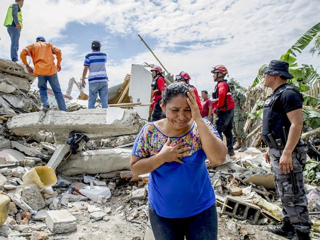 PEDERNALES, ECUADOR - APRIL 17: A woman cries as the search and rescue workers on duty over the collapsed buildings in Pedernales, Manabi Province of Ecuador on April 17, 2016. A woman cries as the search and rescue workers on duty over the collapsed buildings in Pedernales, Manabi Province of Ecuador on April 17, 2016.