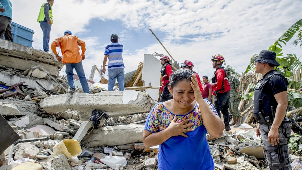 A woman cries as the search and rescue workers on duty over the collapsed buildings in Pedernales, Manabi Province of Ecuador on April 17, 2016.